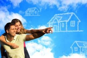 Happy coupleunder the blue sky dreaming of a house.