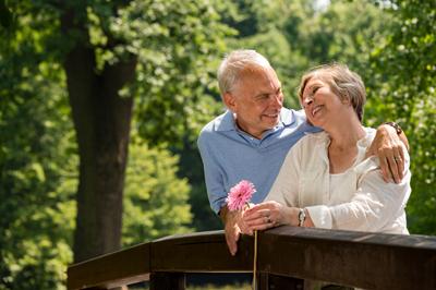 Retired couple romantic hugging in park
